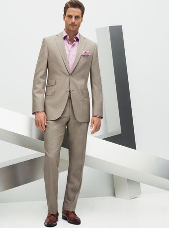 Man wearing a tan suit with pink dress shirt